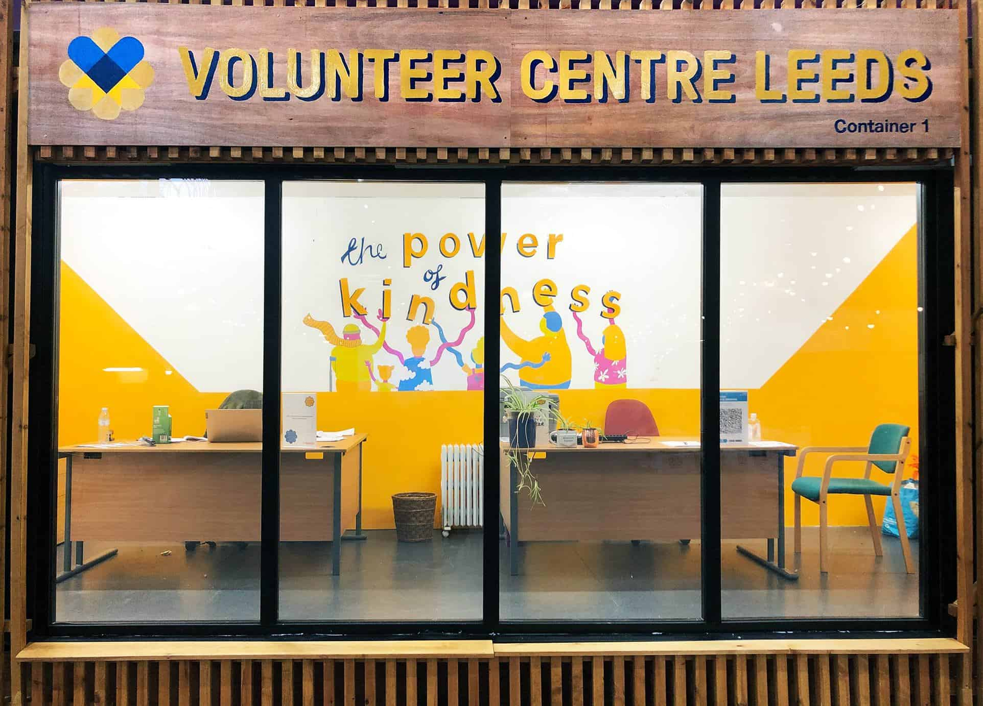 Photo of the front of the volunteer centre, there is a big glass window showing inside the centre where there are two desks and a colourful mural on the back wall which has the words the poser of kindness painted on
