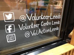Close up photo of the volunteer centre window displaying the social media account names for the volunteer centre @VolunteerLeeds on twitter, Volunteer Centre Leeds on facebook and @VolActionLeeds on instagram